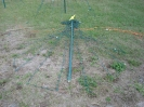Pick the center pole up and lay it on the ground pointing AWAY from the last stake